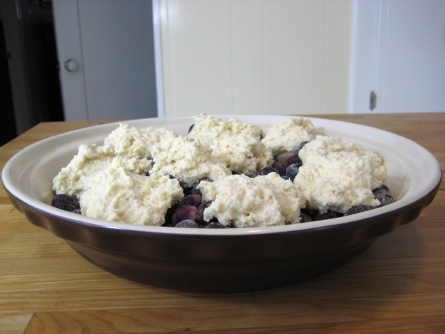 Biscuit dough dropped by spoonful on top of blueberries; ready to bake
