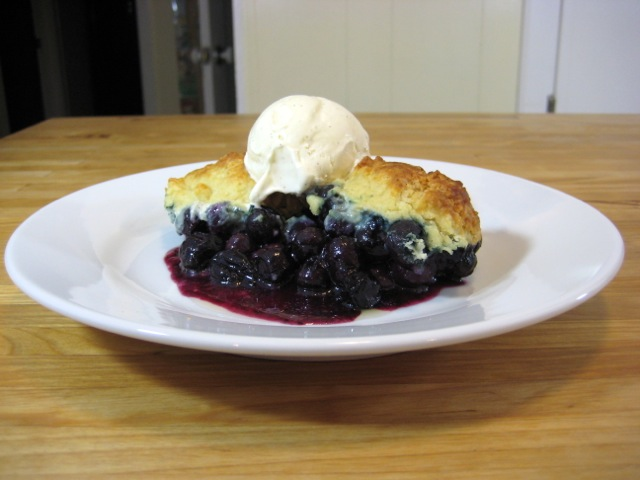 Blueberry cobbler served with a scoop of vanilla bean ice cream