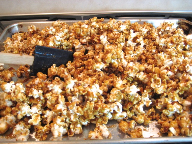 Gently turning and coating the popped corn after 15 minutes of baking