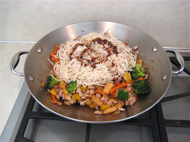 Cooked noodles and sauce added