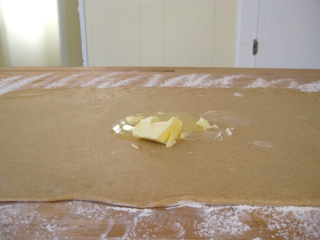 Spreading softened butter on dough