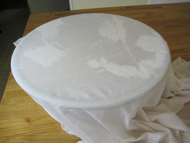 Dough covered with damp cloth, ready to rise