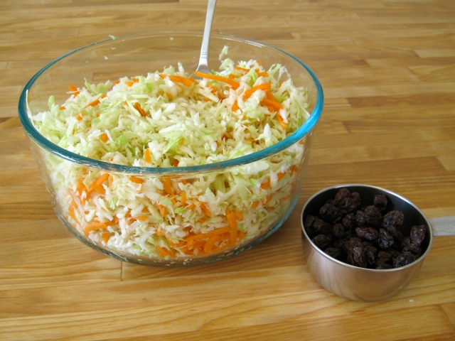 Grated cabbage and carrot in bowl. Raisins ready to be added