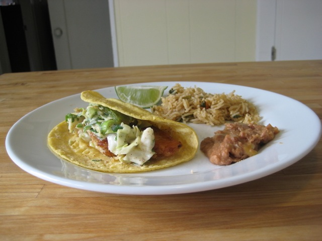 Fish taco on plate with rice, refried beans, and a lime