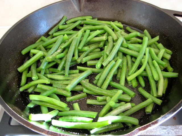 Green beans and salt and pepper added to pan with oil