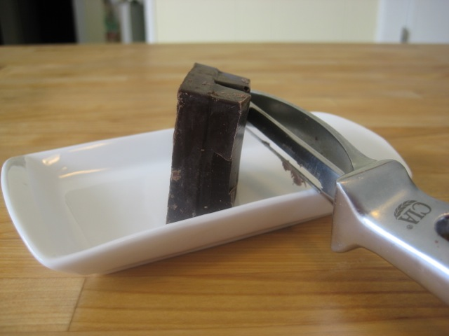 Shaving thin pieces of chocolate from a chocolate square