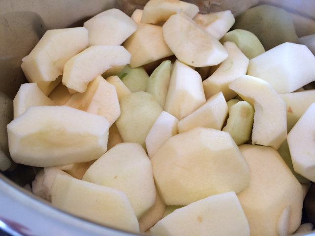 Peeled, cored, quartered apples in pot