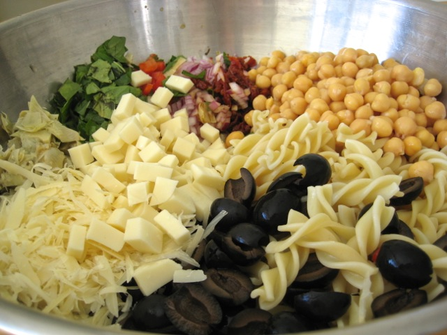 Pasta, veggies, and cheese in a mixing bowl