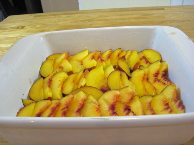 Peaches arranged on top of brown sugar mixture