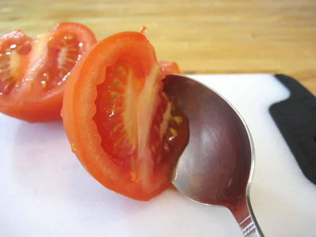 Scooping out the tomato seeds with a spoon