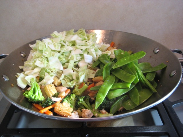 Adding cabbage and pea pods to wok