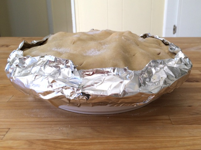 Edge of crust covered with foil strip, ready to bake
