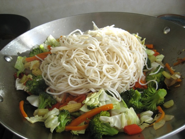 Noodles added to wok