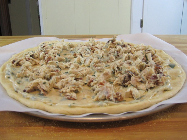 Bacon, chicken, and sauce mixture added to pizza round